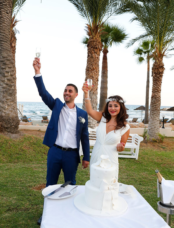 Bride and groom holding champagne glasses, celebrating. Mediterranean Sea on background | city hall Larnaca wedding photography cyprus, civil wedding photography in larnaca