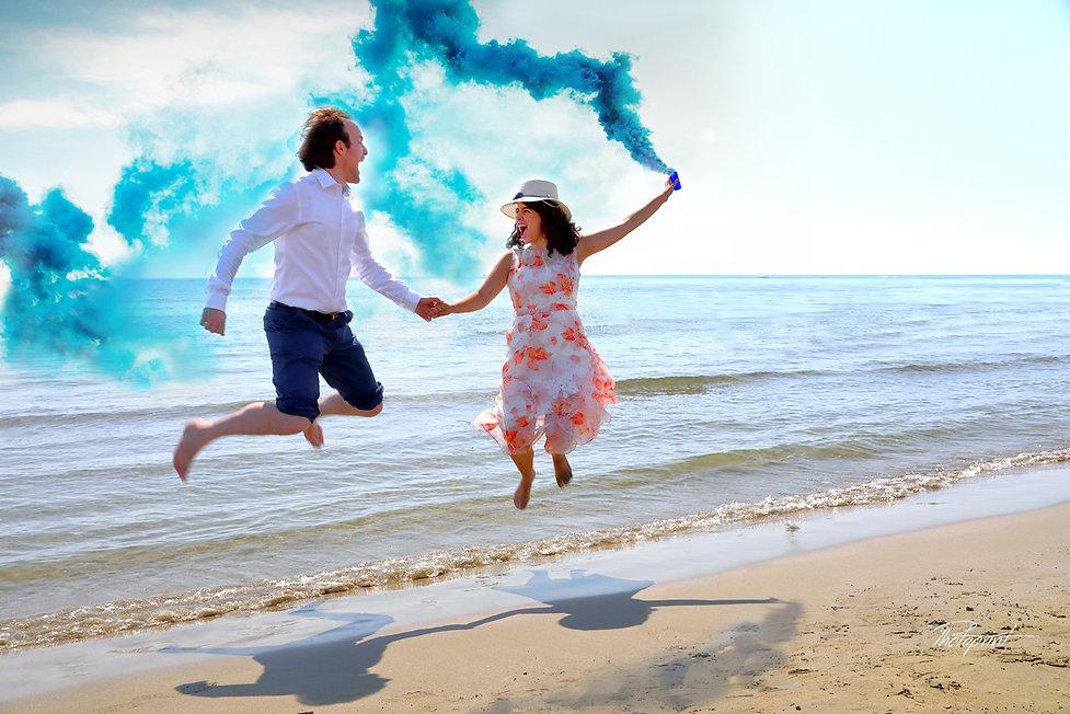Amazing wedding couple by the beach having fun with blue smoke grenade, bomb | cyprus wedding photographer