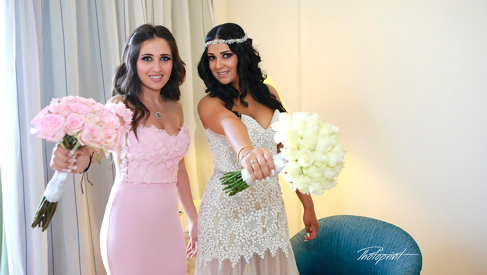 Bride and bridesmaid with wedding bouquets indoor the hotel before the wedding