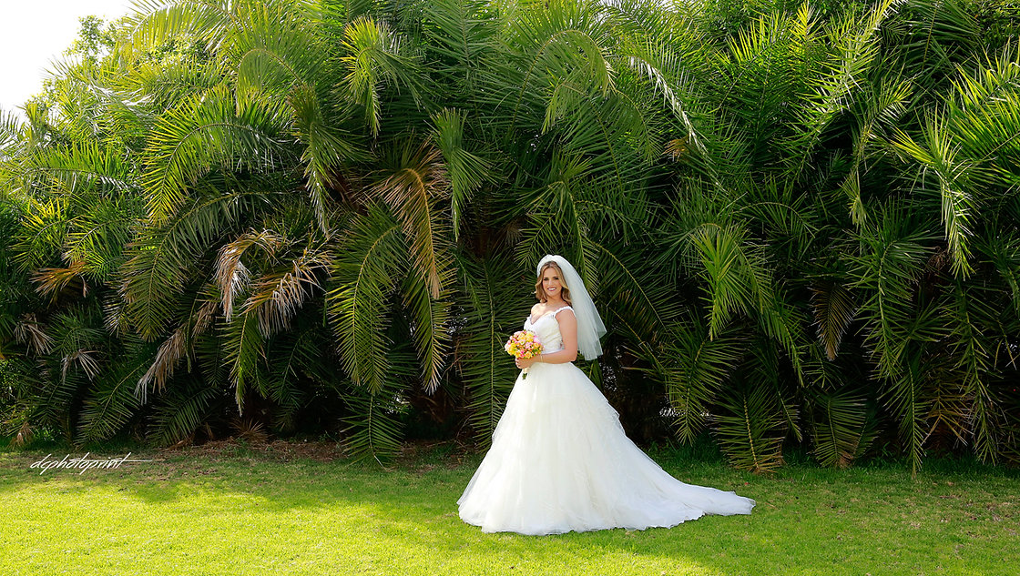 Gorgeous bride in wedding dress with bouquet of flowers posing in the gardens of Palm Peach Hotel in Larnaca. Α lot of palm trees in the background
