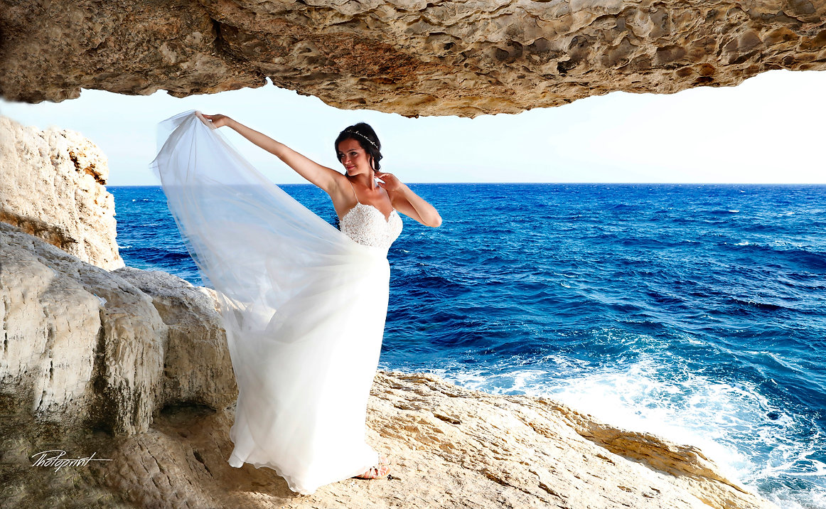 Gorgeous bride in wedding dress with bouquet of flowers posing on Gape Greco near Ayia napa, cyprus |  best wedding photographer in ayia napa cyprus, own hall ayia napa wedding photographer