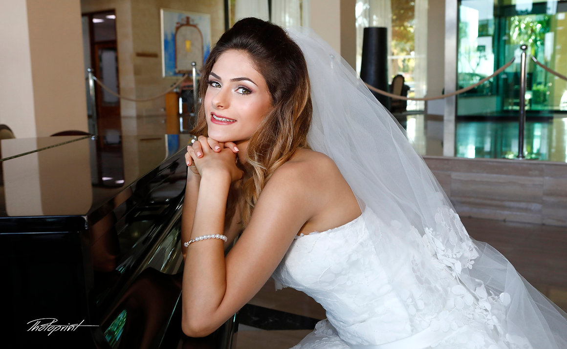 beautiful young bride, Mireille in a luxurious lace wedding dress. She sits on a black piano indoors in Grecian Park Hotel at Protaras, cyprus  | wedding photographers protaras, wedding photographers protaras,wedding protaras photographer
