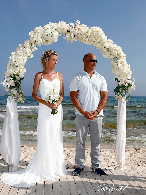 Wedding on the beach, wedding arch decorated with flowers on Mediterranean sand beach, Wedding couple holding hands on sunset.  The blue Mediterranean Sea on background | cyprus wedding photographer | Packages ,ayia Thekla  best wedding photos cyprus, civil ayia Thekla  wedding photography