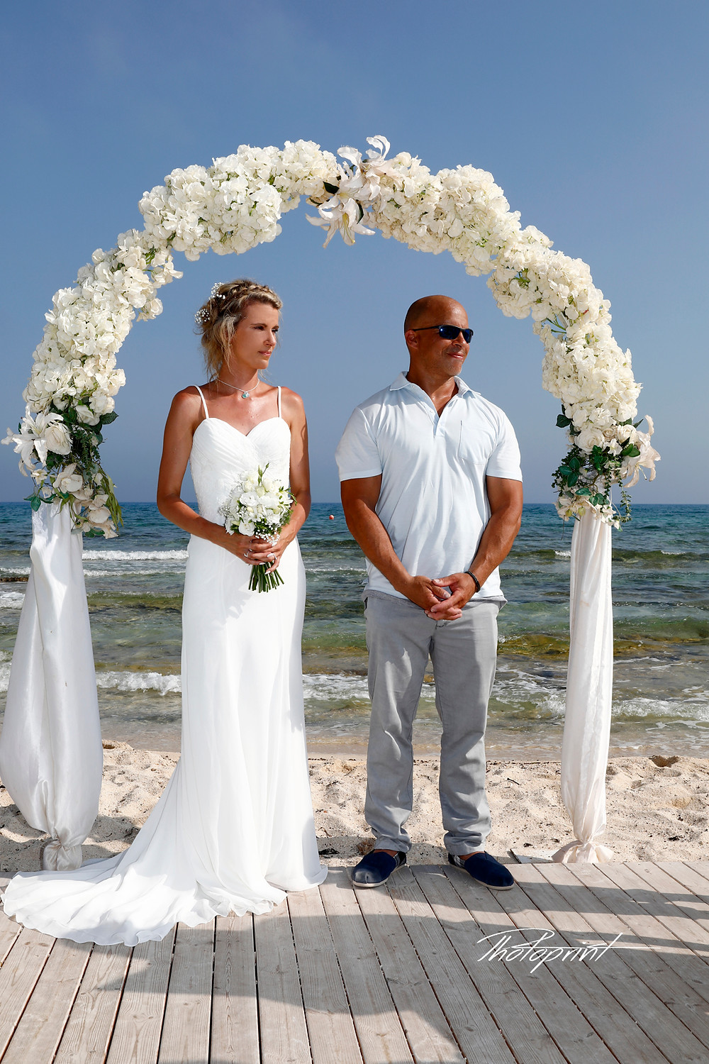 Wedding on the beach, wedding arch decorated with flowers on Mediterranean sand beach, Wedding couple holding hands on sunset. The blue Mediterranean Sea on background