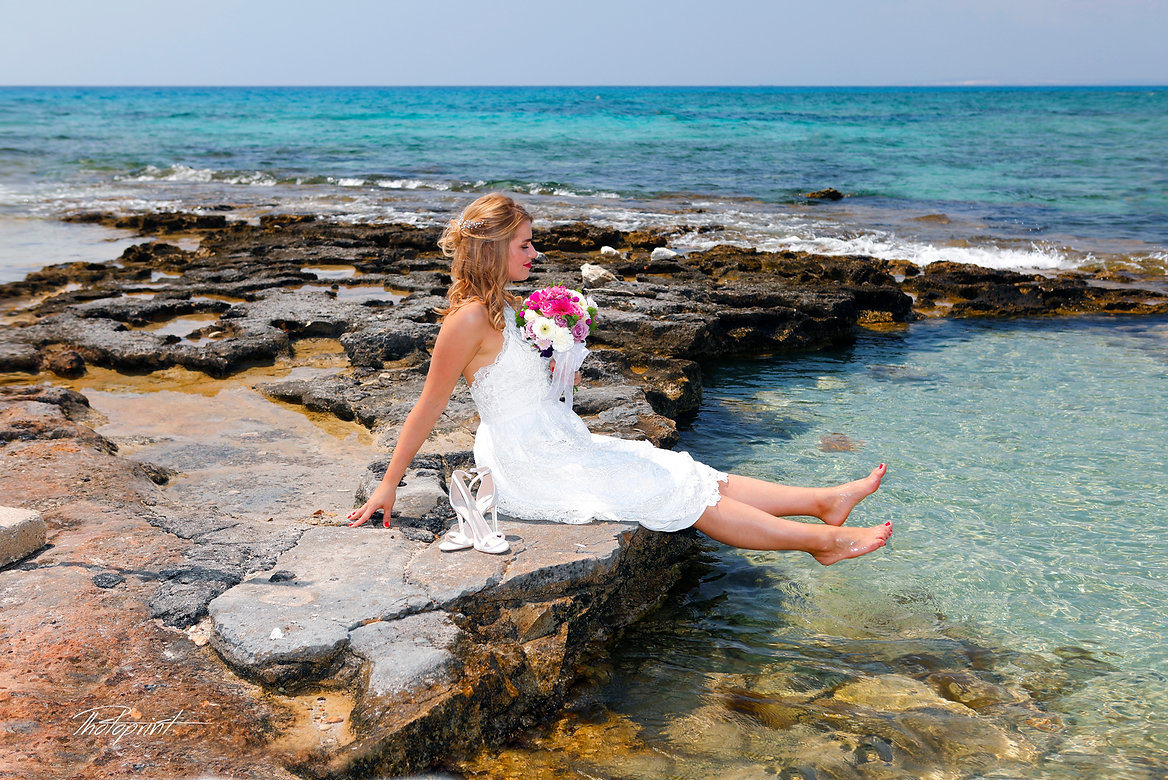Gorgeous bride in wedding dress with bouquet of flowers posing in ayia napa beach |  wedding photography ayia napa cyprus, ayia napa municipality wedding ceremony, ayia napa municipality wedding ceremonies, ayia napa wedding reception venues.