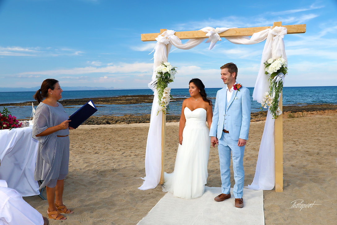 Side View wedding ceremony standing Atilla and Sandra by the beautiful beach Agia triada | photographers in Agia triada weddings