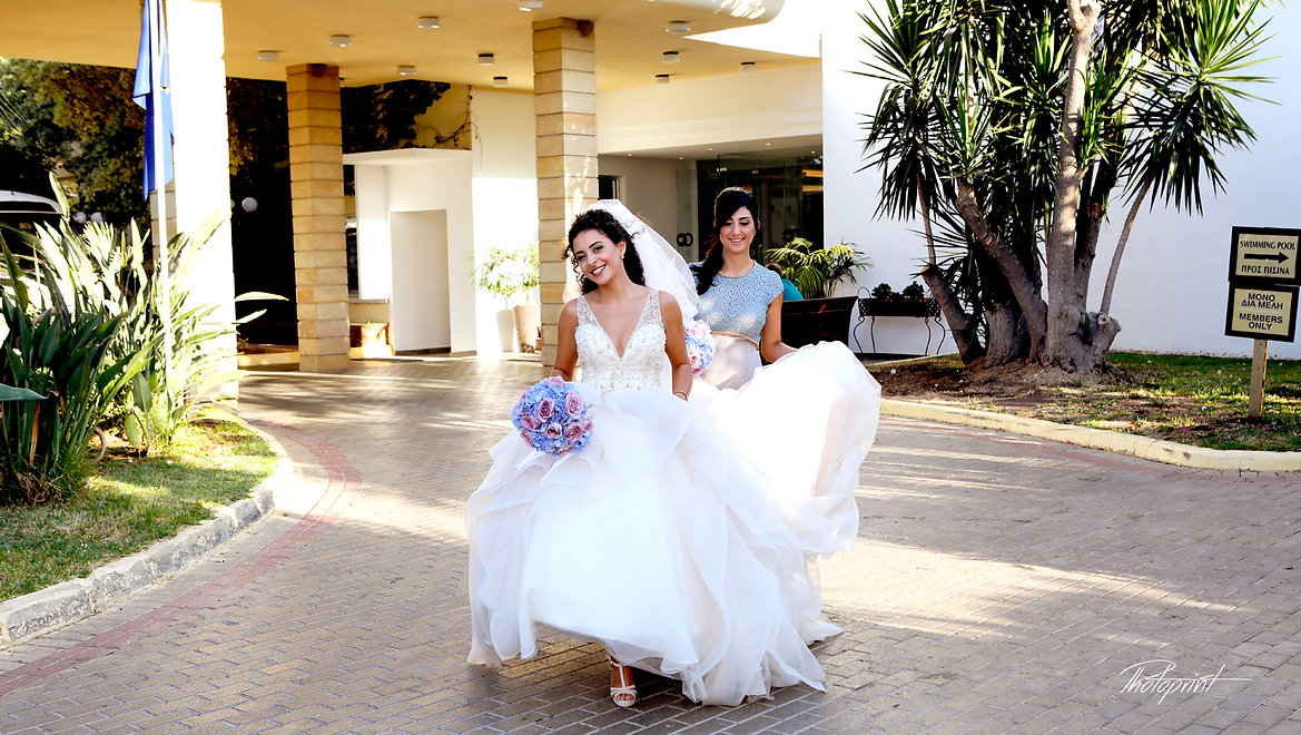 Bride and bridesmaid with wedding bouquets  coming for the wedding ceremony |  larnaca wedding photo prices,  larnaca wedding photography packages, larnaca cyprus wedding photographers cheap