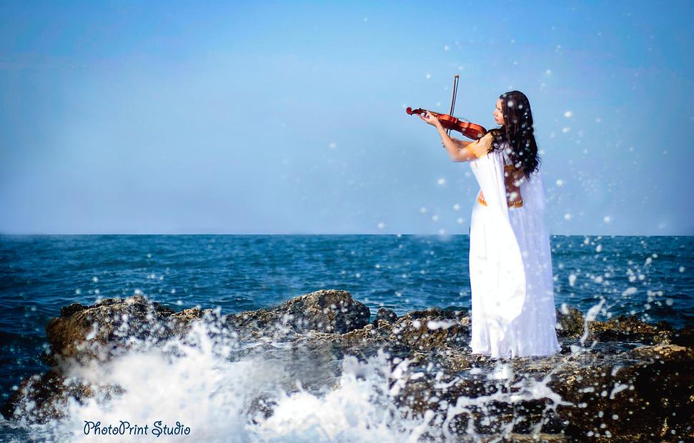 Τhe bride plays with her violin a beautiful melody on the edge of the rock, the sea mines are thrown in the air