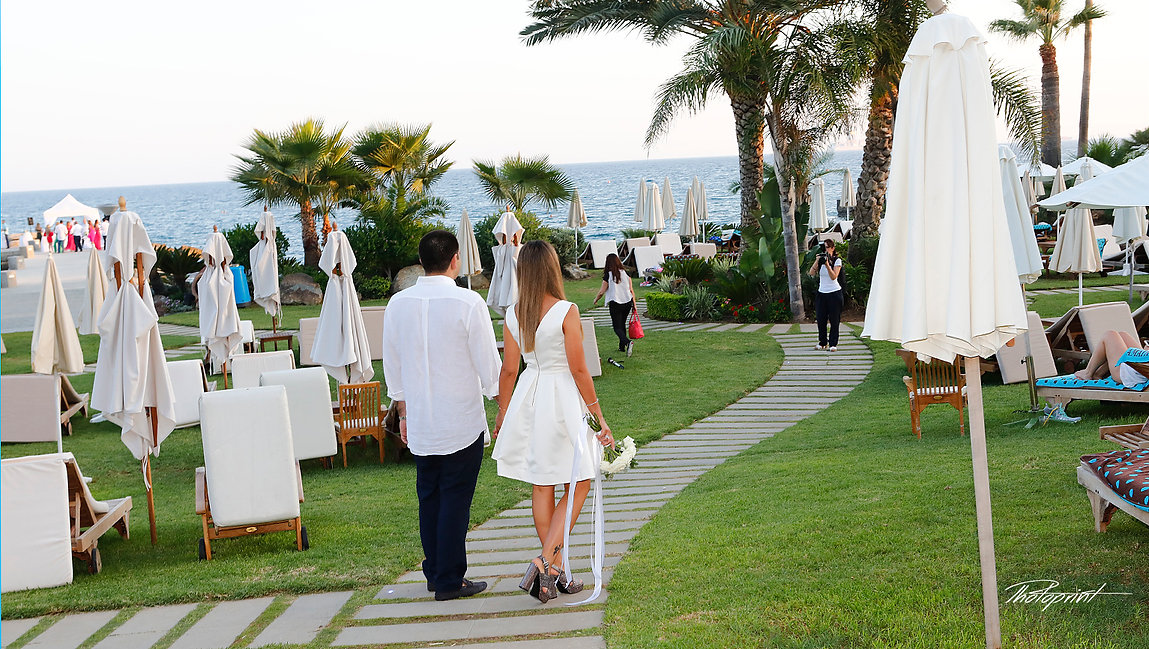 Beautiful and gentle wedding photo session outdoors of the elegant couple going to their wedding through the Amathus  beach Hotel, gardens. Mediterranean Sea on background |  limassol wedding venues photography, wedding limassol photography cyprus