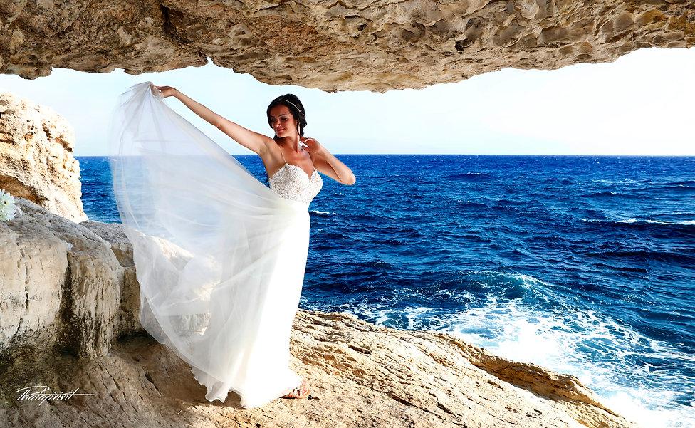 Gorgeous bride in wedding dress posing at Cape greco beach. Blue Mediterranean Sea on background | wedding portfolio