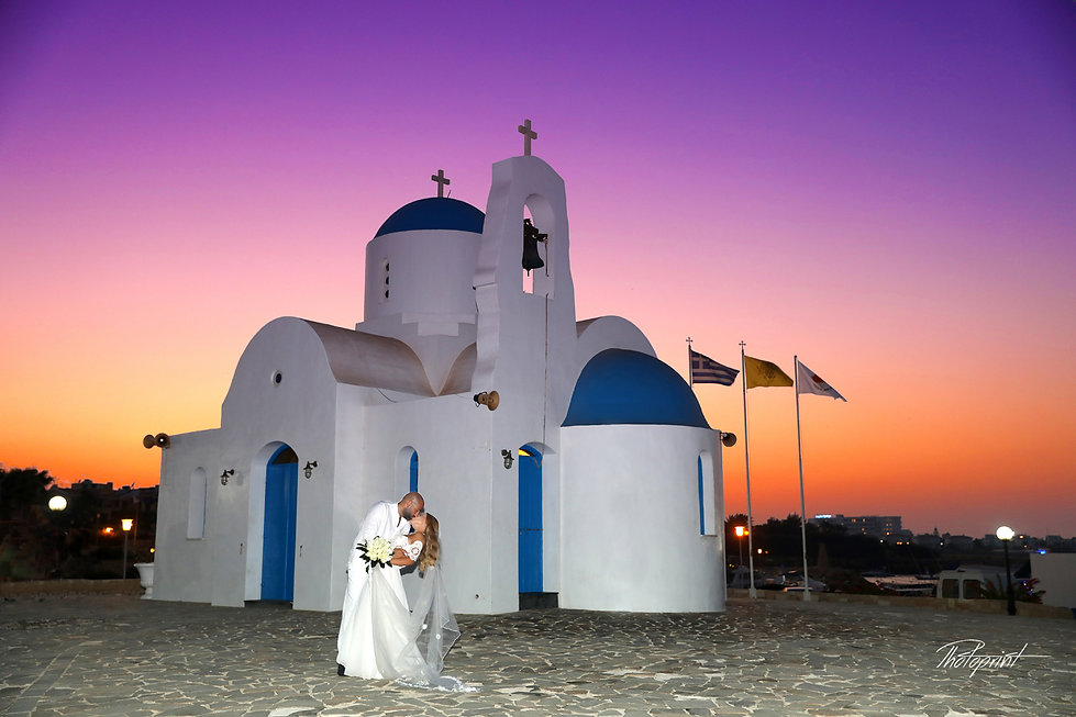couple kissing after the ceremony with background agios Nikolaos church at sunset in Protaras cyprus