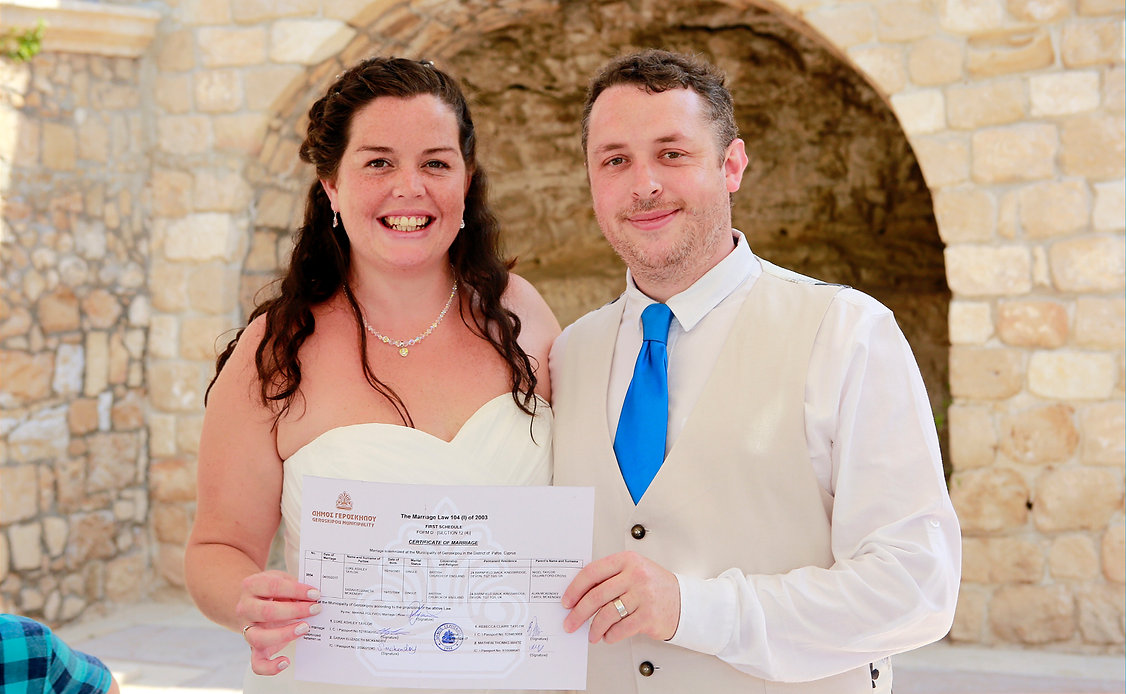 Happy bride and groom show us the registration form on the wedding day at Geroskipou Municipality in Paphos | wedding photographers paphos cyprus, cyprus wedding photography best prices, wedding photographer paphos