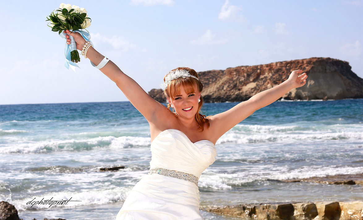 Gorgeous bride in wedding dress with bouquet of flowers posing in Paphos beach | best wedding photography websites cyprus, cyprus cheap wedding photographers price