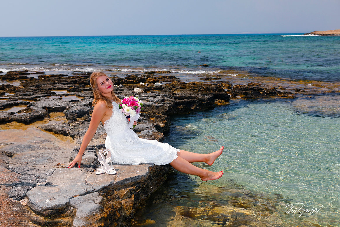 Gorgeous bride in wedding dress with bouquet of flowers posing by the sea | ayia napa wedding photographers, ayia napa wedding photography packages, photographer ayia napa cyprus