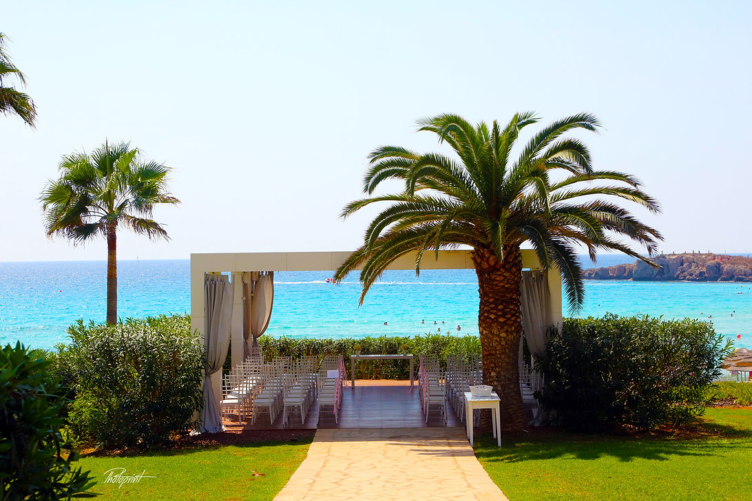 The Wedding location decorated with flowers on tropical sand beach outdoor on Nissi Beach Resort in Ayia Napa, Cyprus. | cyprus wedding photographer Nissi beach Resort ayia napa