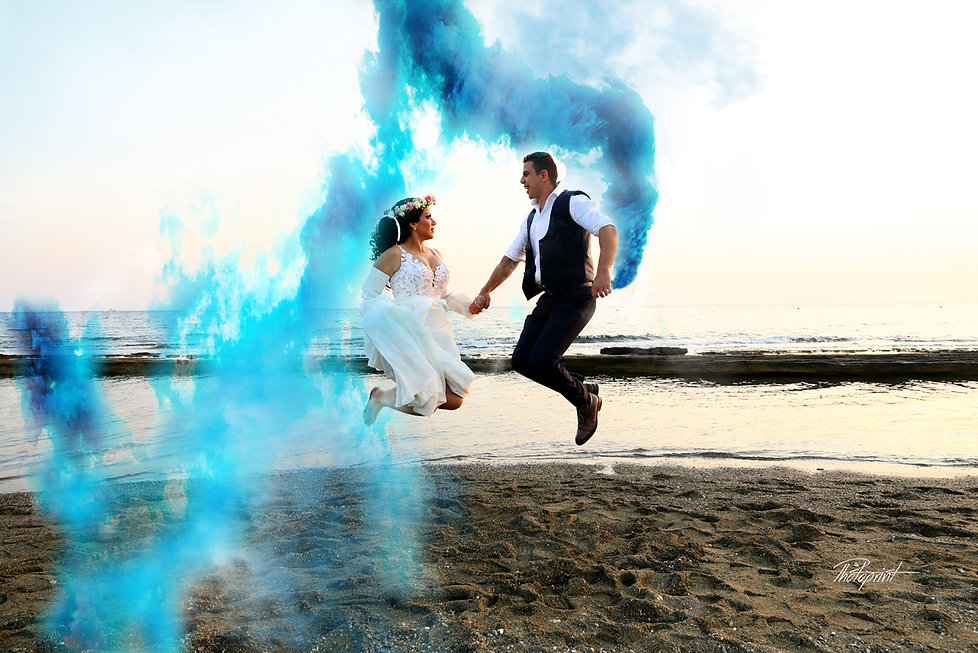 Cheerful young  wedding couple smiling jumping on the beach at sunset time