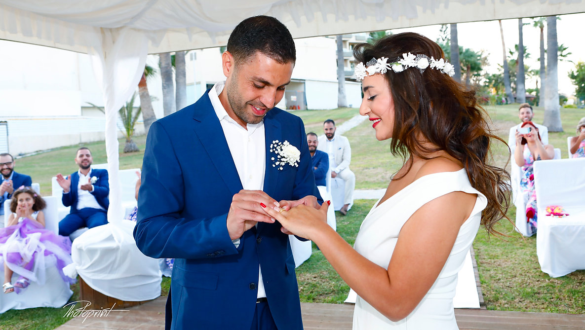 Close up detail of groom putting wedding ring on bride's finger during the wedding ceremony  in Golden Bay Beach Hotel, Larnaca | lebanese wedding in cyprus, Wedding Venues in Cyprus for lebanese