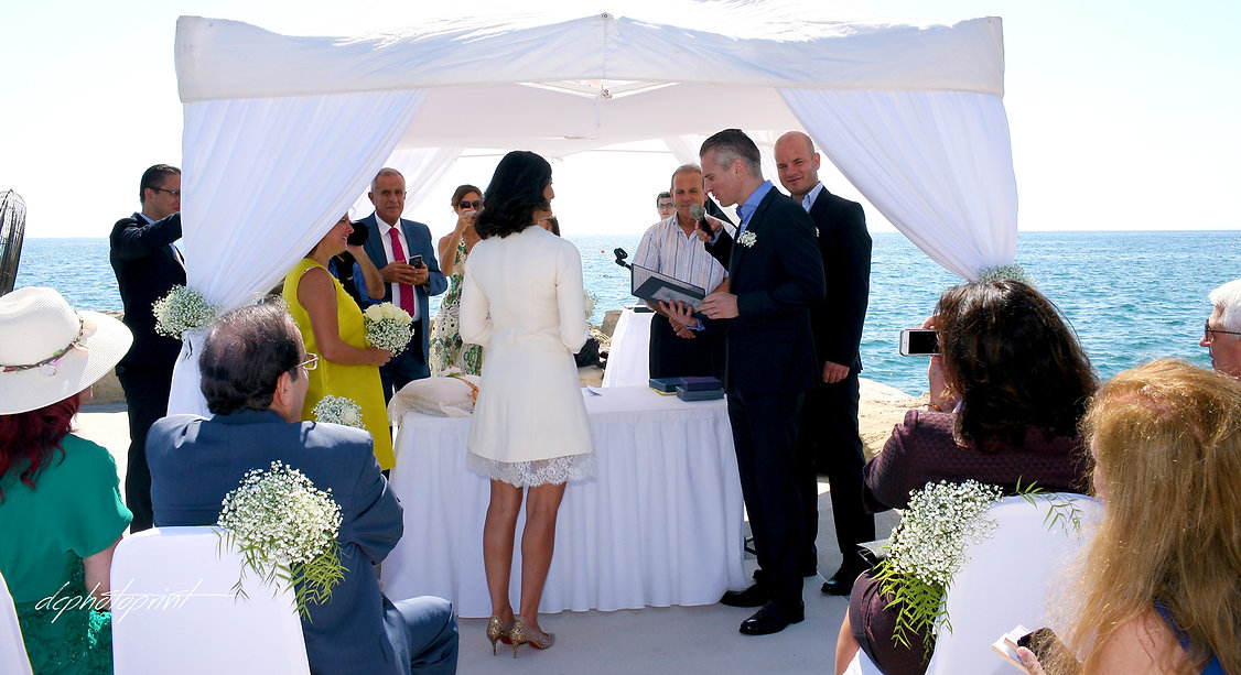Groom  swearing lifetime loyalty the wedding ceremony  in Amathus  Beach Hotel, Limassol cyprus.  magnificent Mediterranean Sea in the background | wedding photographers limassol, wedding limassol photography cyprus
