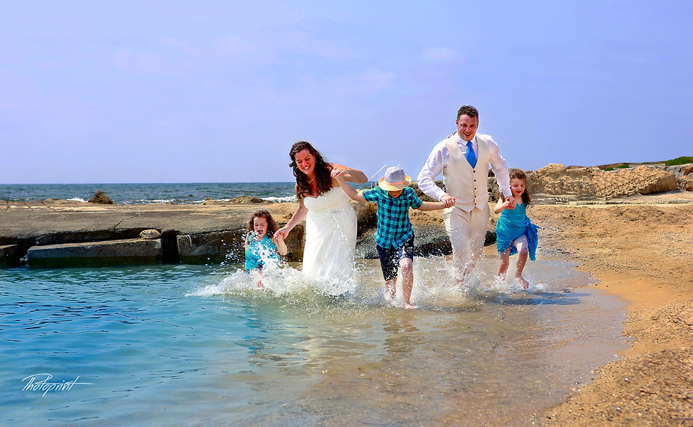 happy Beautiful wedding couple with Children in running in water
