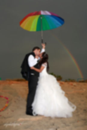 Bride and groom kissing outdoors, the uranium arc in the background