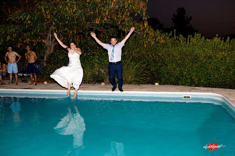 The newlyweds jump into the water of the pool, the guests laugh | cyprus Paphos wedding photography  cost, civil weddings in Paphos