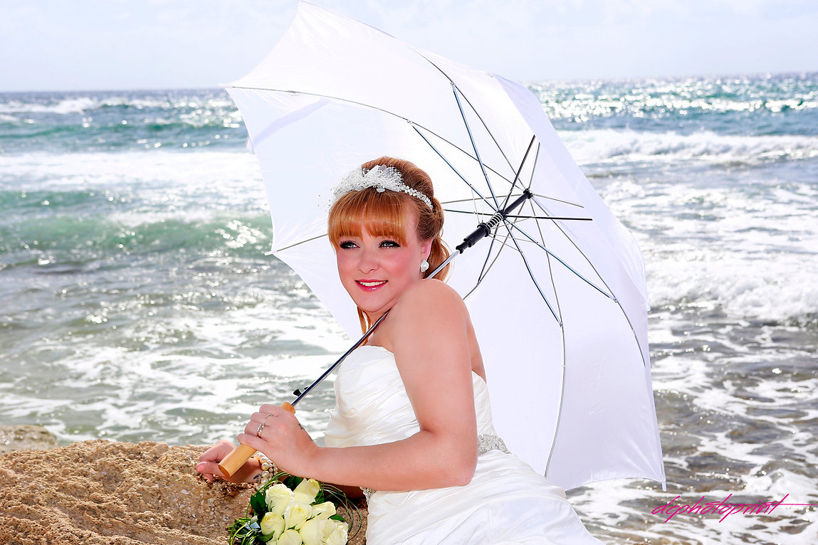 Close-up portrait of gorgeous beautiful bride in white dress with amazing hair style and make up, holding bouquet and  umbrella. Blue Beautiful  Mediterranean Sea on background |  cyprus sunset images wedding photographers paphos, wedding photographers in paphos
