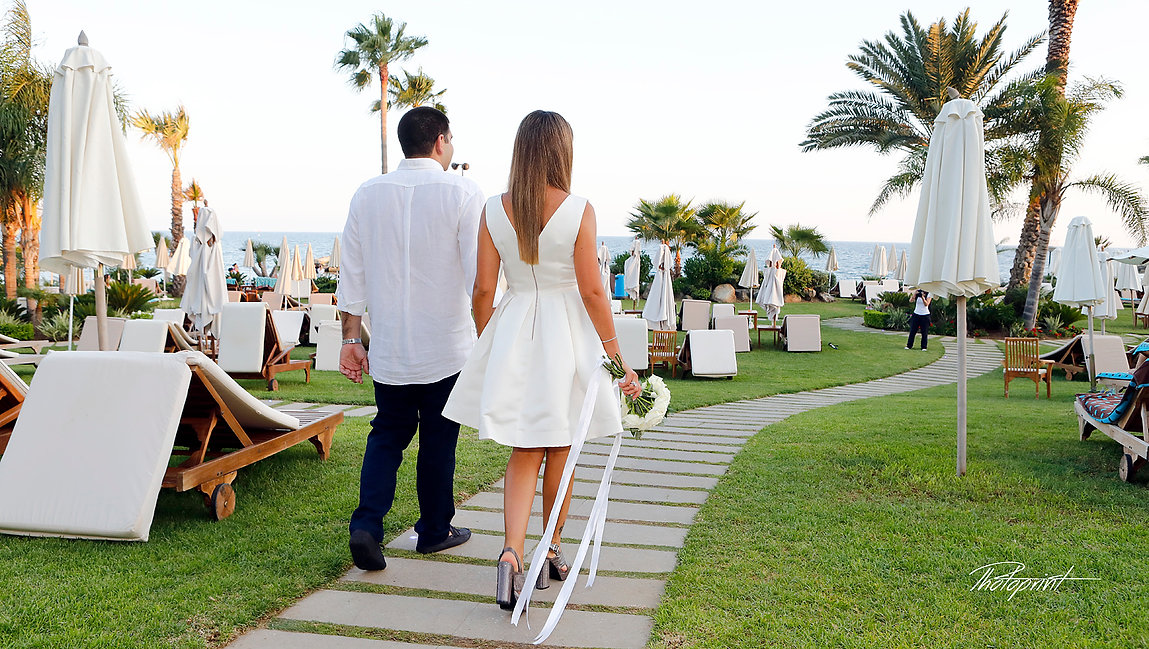 Beautiful and gentle wedding photo session outdoors of the elegant couple going to their wedding through the Amathus  beach Hotel, gardens | cyprus wedding venues photographer limassol, wedding limassol photographer