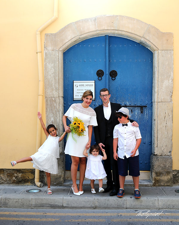 Happy couple standing outside the town hall Larnaca holding some children before the wedding | cyprus wedding photographer larnaca, city hall Larnaca wedding photography cyprus