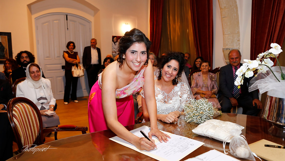 Attractive happy bridesmaid signing the wedding contract in municipality of larnaca | wedding photography in Larnaca best weddings