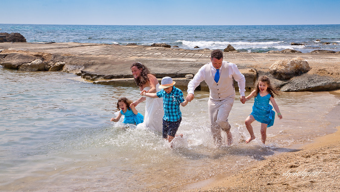 Beautiful couple on the paphos beach with their children having fun at the seaside | famous wedding photographers cyprus, photography prices cyprus, wedding photographer in cyprus