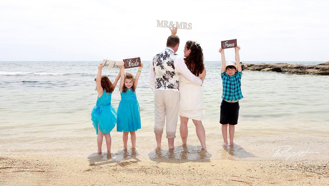 Romantic bride and groom having fun at the seaside with their children, paphos beach |  cyprus wedding photographers yeroskipou, cyprus average cost of wedding photography per hour, budget wedding photographer cyprus