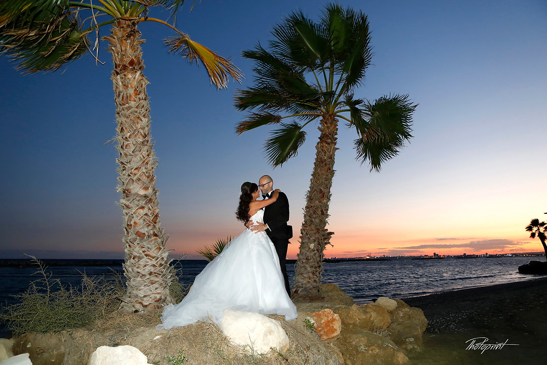 Romantic picture of the marriage couple through two palm trees night next to the sea at larnaca | Larnaca photographers cyprus,Beach Weddings Packages larnaca, best photographers in larnaca, Civil ceremony at Larnaka town hall