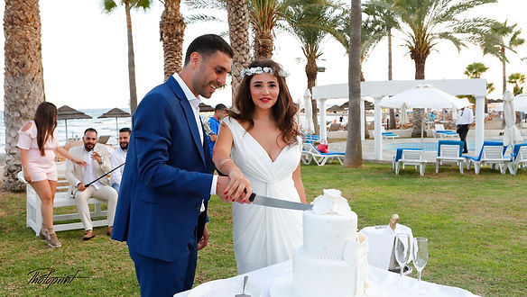 Beauty bride and handsome groom are cutting a wedding cake at reception | cyprus wedding larnaca wedding photography prices, cyprus wedding larnaca photography ideas