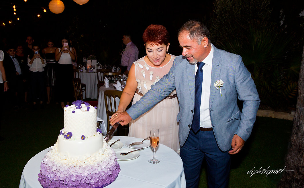 Bride and Groom cutting wedding cake at reception | best paphos cyprus wedding photography websites, best cyprus wedding photographers paphos