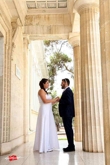 Beautiful israeli couple standing outdoor the town hall Paphos holding hands after the wedding | israeli  wedding photography prices in yermasoyia, best israeli wedding photographers in cyprus
