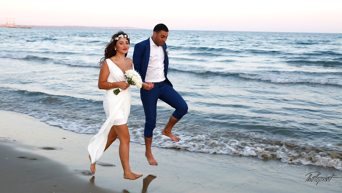 Beautiful picture of romantic young couple having a walking on the sea shore  | cyprus wedding photography best prices, Larnaca beach hotel wedding photography