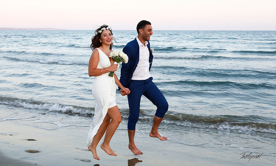 Cheerful young  wedding couple smiling jumping on the beach at sunset time | wedding portfolio