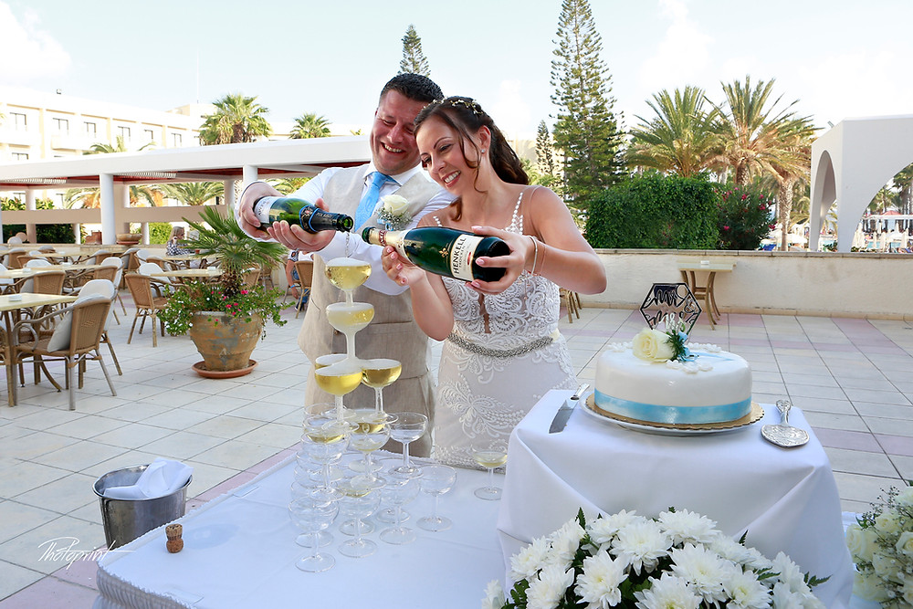 Wedding photo of beautiful smiling just married couple pouring champagne into glasses, at LOUIS PHAETHON BEACH HOTEL in Paphos