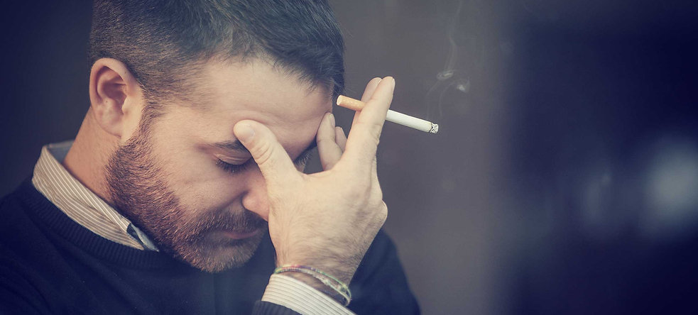 a man worrying about his smoking while holding cigarette