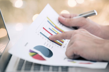 man's-hands-at-a-laptop-computer-holding-a-pen-and-a-document-depicting-a-piechart-and-bar-graph-report.jpg