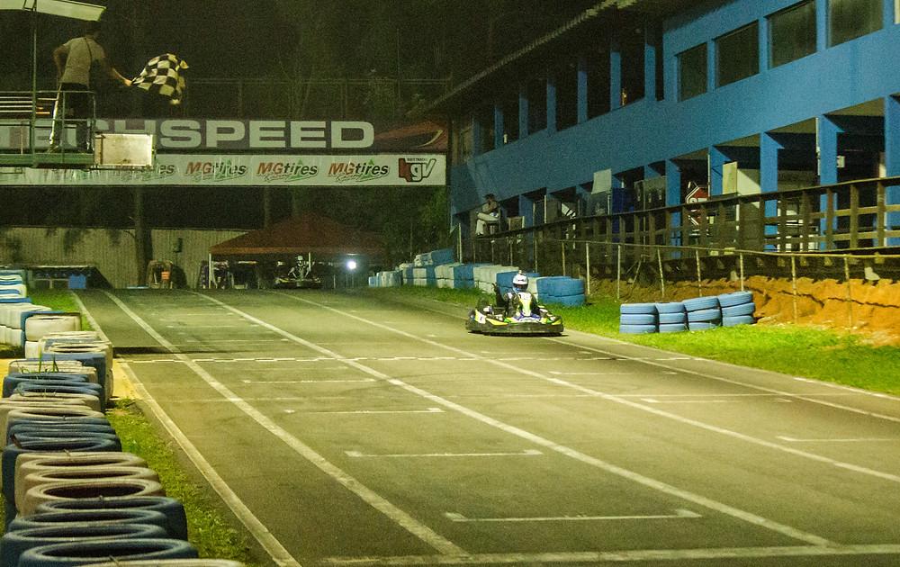 Alexandre Gregoski (BTR) recebe a bandeirada enquanto a presidente recebia o sim pela família. PKL Paulista Kart League