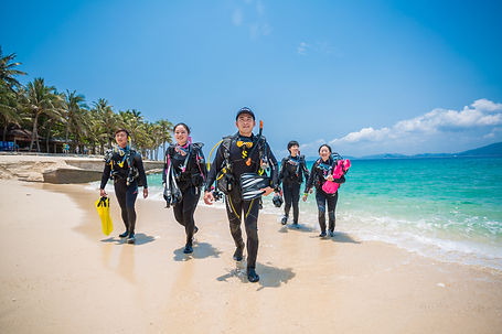 Group of PADI divers coming back from shore dive