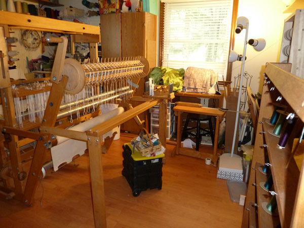 Loom with sectional warp beam in a messy studio.