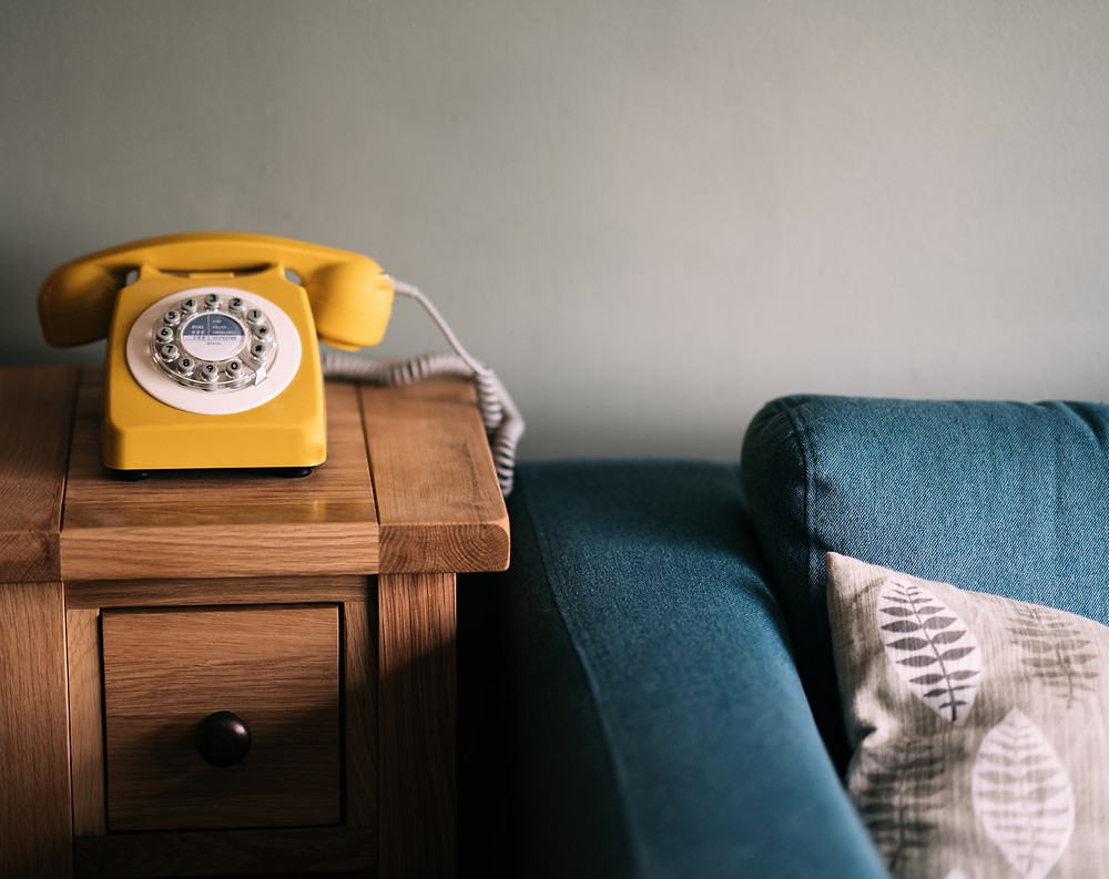 Image of yellow dial telephone on wooden table next to blue couch.