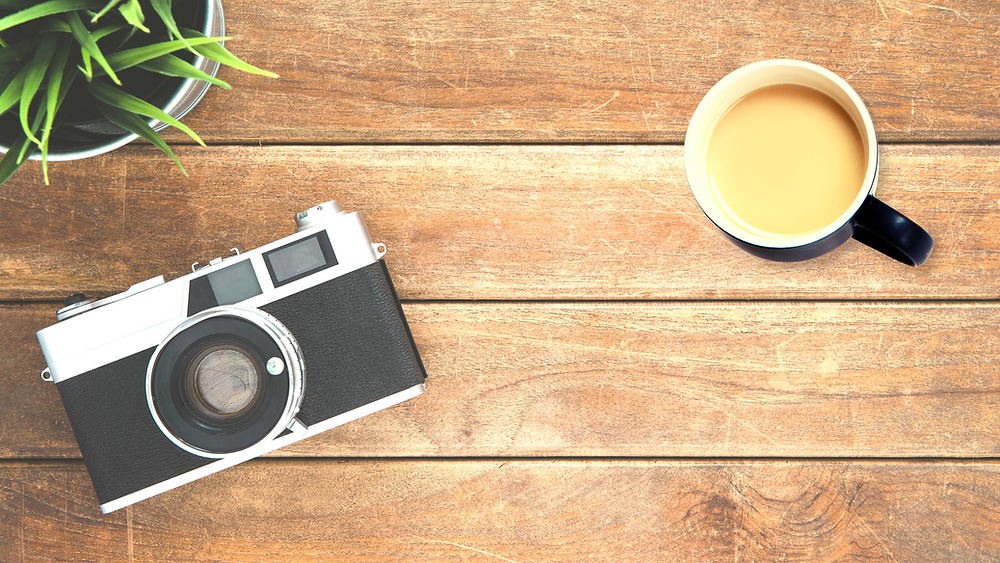 activity vs action and setting goals - picture of camera, plant and coffee on a desk