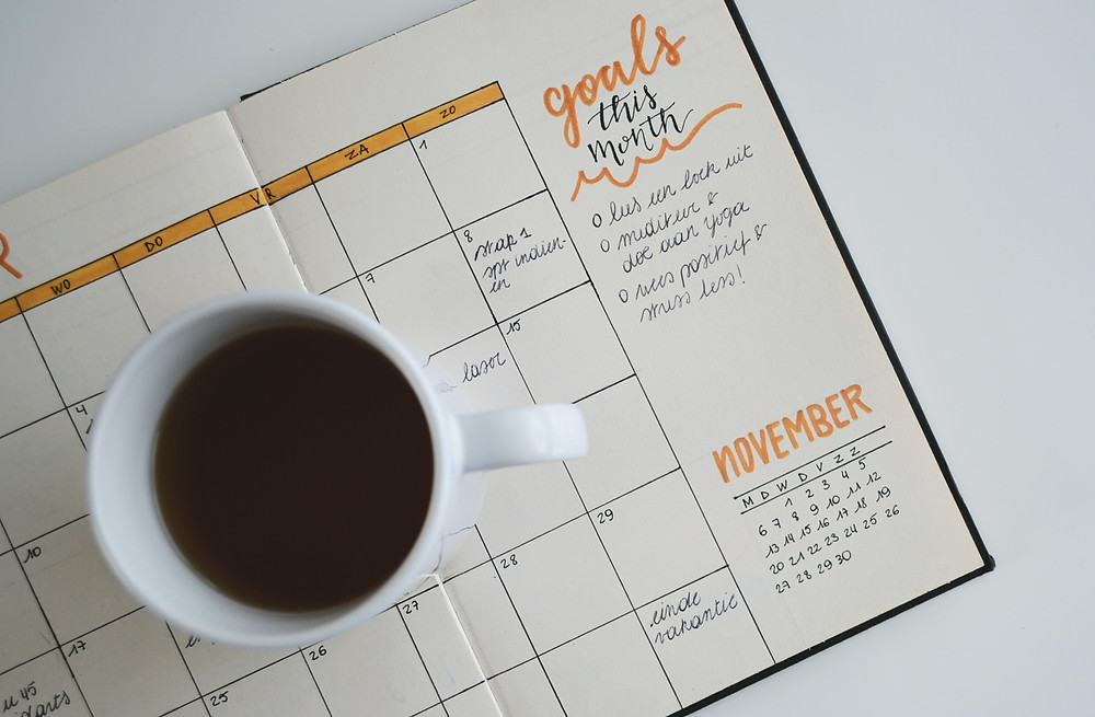 calendar diary with cup of coffee on top