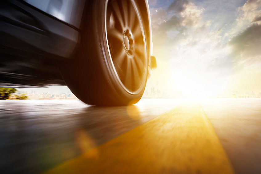 Low angle side view of car driving fast at sunset with motion speed effect.jpg