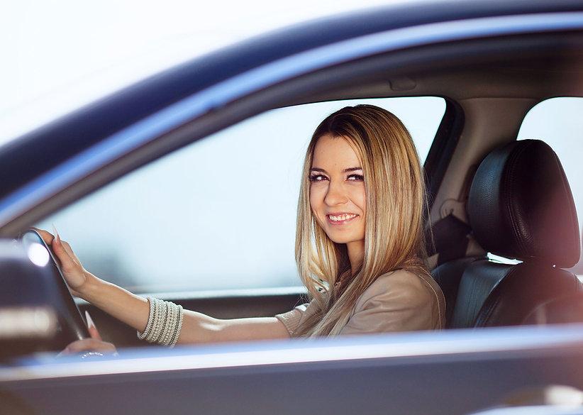 Beautiful blond girl in her car.jpg
