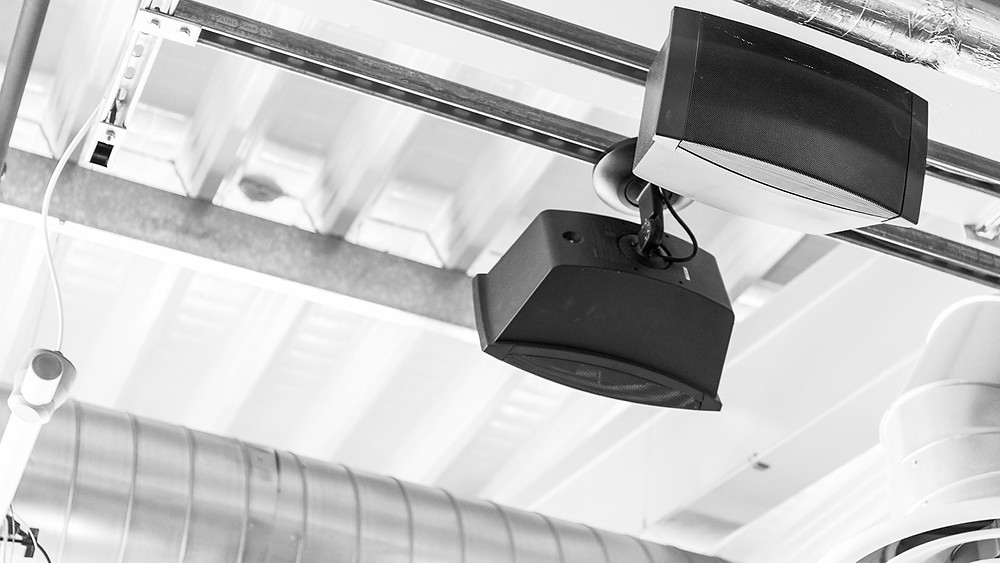 Two ceiling hung loudspeakers as part of a fitness audio system
