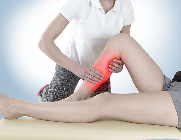 Doctor is stretching woman leg on physio